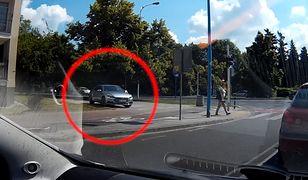 Srebrny volkswagen zaparkował na samym środku chodnika.