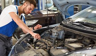 Portrait of a mechanic servicing a car at his workshop