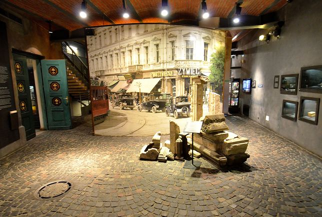 Fragmenty gzymsów i portali pochodzące ze zburzonego Zamku Królewskiego. W tle zdjęcie kamienicy Pinkusa Lothego, po lewej wejście do Sali Małego Powstańca