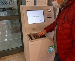 Automat wymienia monety na banknoty. Ludzie ustawiają się w kolejkach