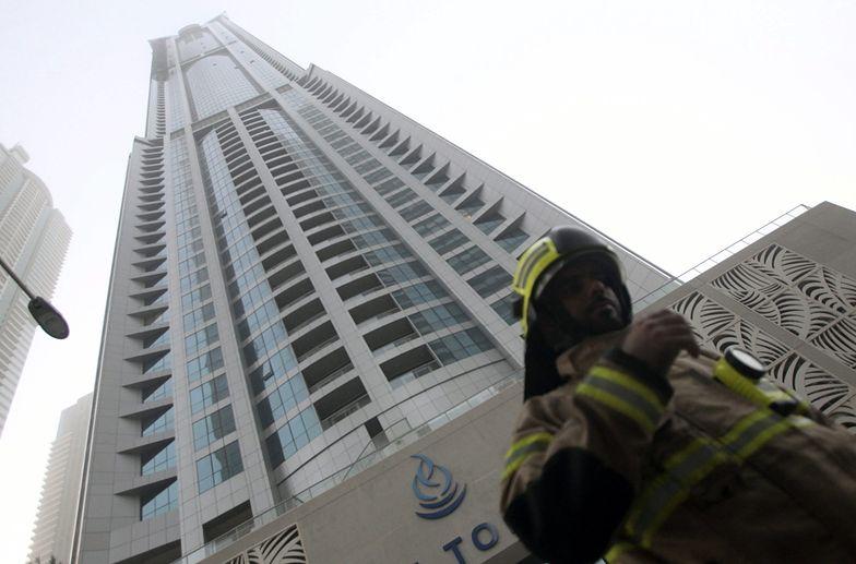 """Strażak przed wieżowcem """"The Torch"""" w Dubaju po pożarze</br>"""