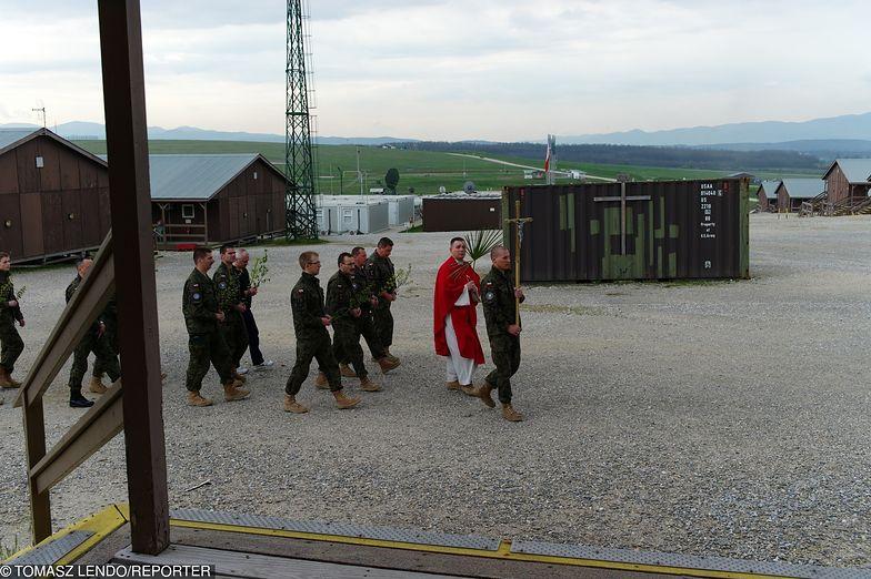 Kapelan wojskowy razem z żołnierzami na misji zagranicznej.