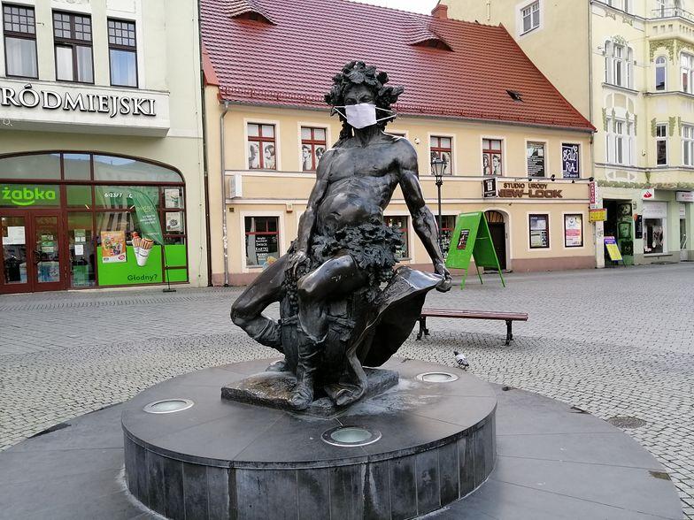 Pomnik w centrum miasta zyskał maseczkę ochronną. Mieszkańcy miasta korzystają z takich zabezpieczeń znacznie rzadziej.