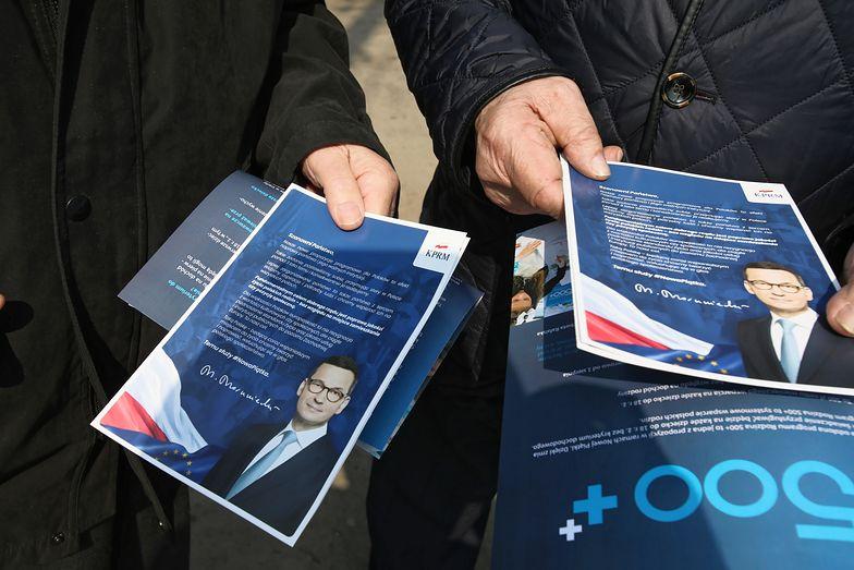 Mieszkańcy Otwocka z ulotkami reklamującymi nowe programy socjalne rządu.
