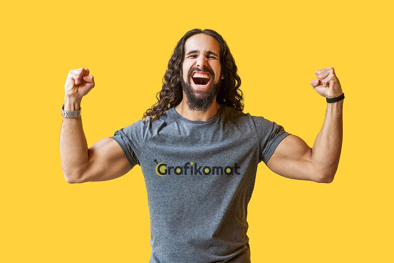 Yes! Portrait of happy rejoicing bearded young man with long curly hair in grey tshirt standing, raised arms and celebrating his victory, screaming . indoor studio shot isolated on yellow background.