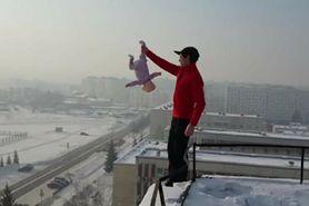 Nieodpowiedzialny ojciec. Trzymał niemowlę za nóżkę, stojąc na dachu wieżowca