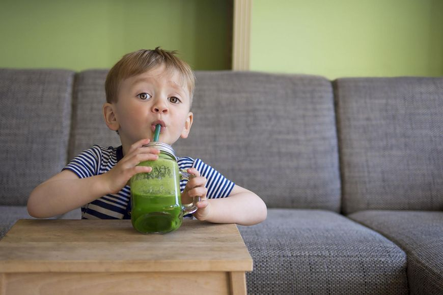 Dziecko z koktajlem z zielonych warzyw