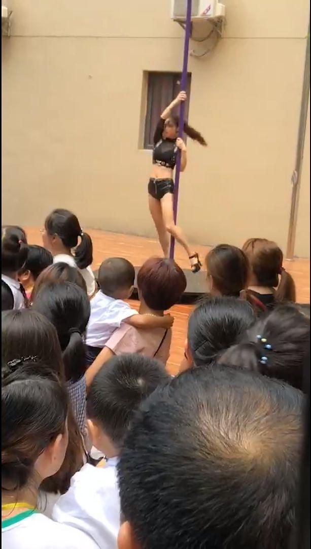 Pole dancerka tańcząca przed tłumem przedszkolaków.