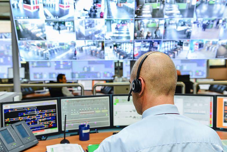 Człowiek przy ekranach monitoringu