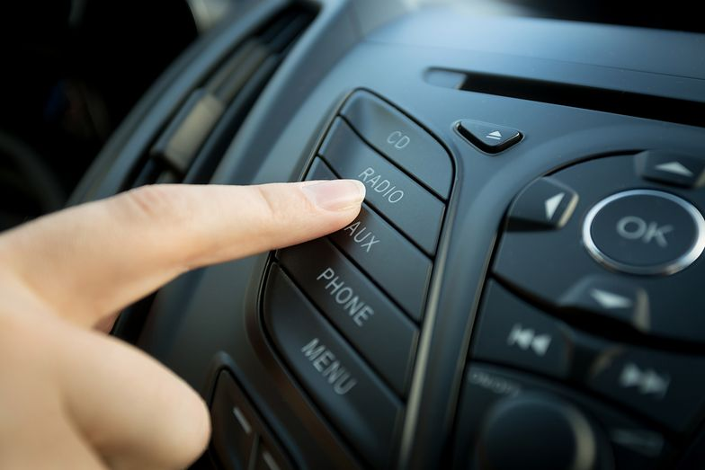 Closeup photo of female finger pressing radio button on car control panel