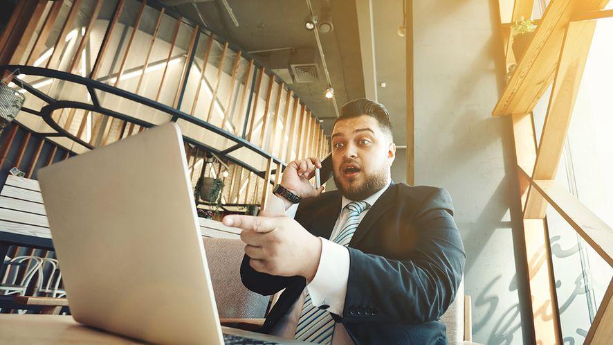 Zdziwiony biznesmen przy laptopie z depositphotos