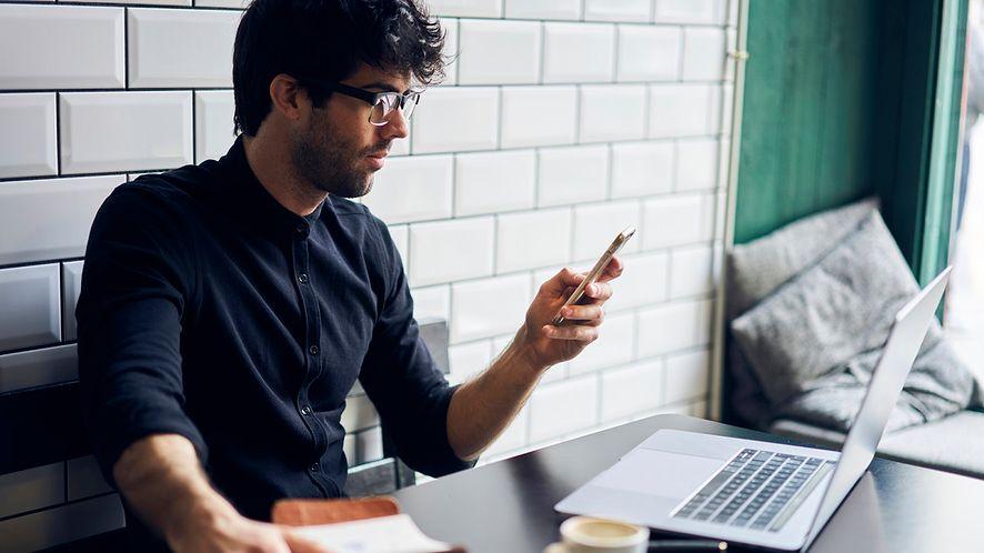 Mężczyzna korzystający ze smartfonu i laptopa z depositphotos