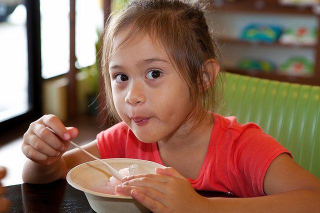 Dziewczynka z apetytem jedząca posiłek