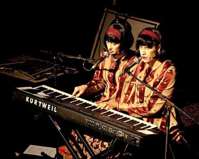 Bliźniaczki syjamski grające na fortepianie