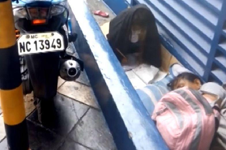 Bezdomna dziewczynka z Manili odrabia lekcje w strugach deszczu