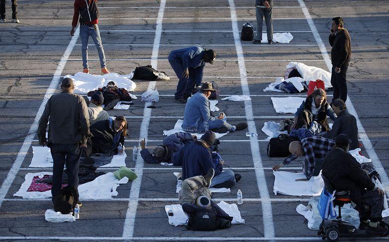 Koronawirus w USA. Bezdomni śpią na ogrodzonym siatką parkingu