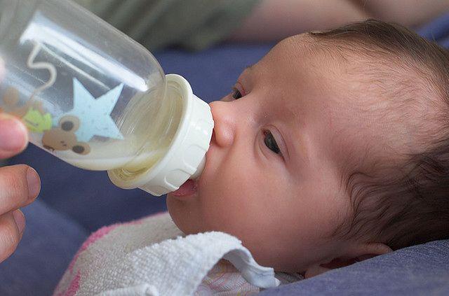 Noworodek pijący mleko z butelki