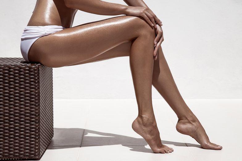 Beautiful woman tan legs. Against white wall.