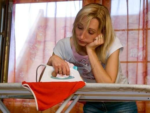 Zmęczona kobieta w czasie prasowania