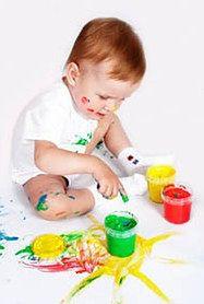 Maluszek bawiący się farbami
