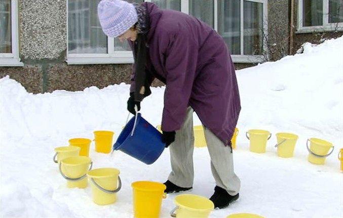 Kobieta przygotowuje wiaderka z wodą
