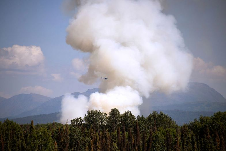 TALKEETNA, AK - JULY 03: A helicopter passes by as smoke rises from a wildfire on July 3, 2019 south of Talkeetna, Alaska near the Gorge Parks Highway. Alaska is bracing for a dangerous fire season with record warm temperatures and dry conditions in parts of the state. (Photo by Lance King/Getty Images)